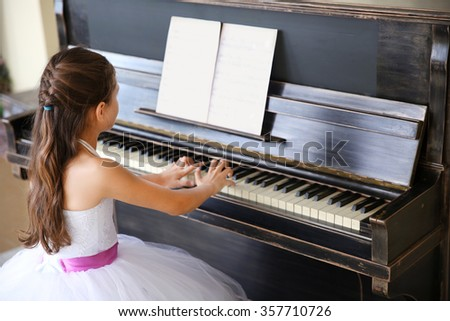 Attractive little princess girl plays piano - stock photo