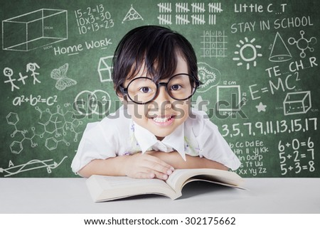 Attractive little student smiling on the camera with a book on the table, shot in the class with scribble background on the chalkboard - stock photo