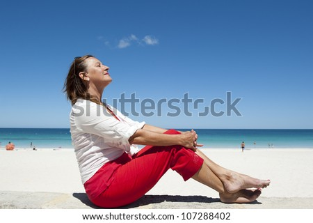 Attractive looking mature woman sitting relaxed and happy on wall overlooking beach, isolated with ocean and blue sky as background and copy space. - stock photo