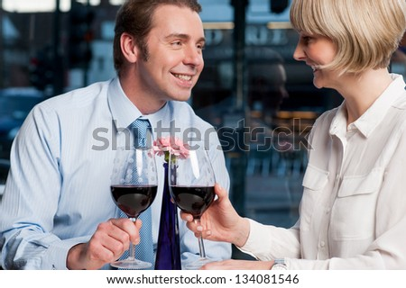 Attractive love couple toasting red wine in open-air cafe.