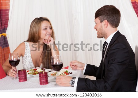 Attractive loving couple enjoying a romantic meal by candlelight at a stylish restaurant as they celebrate Valentines or their anniversary - stock photo