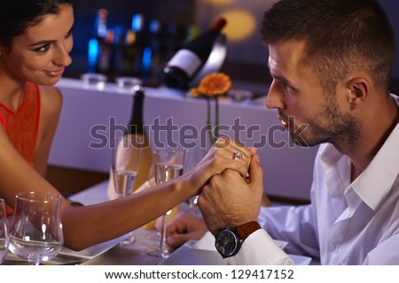 Attractive loving couple holding hands at dinner table, looking affectionate. - stock photo