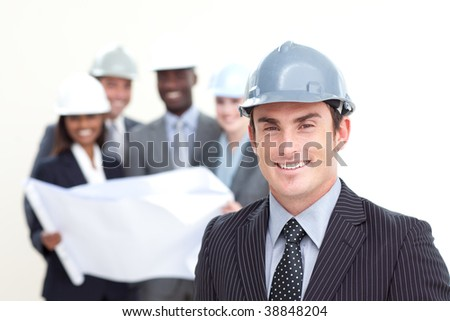 Attractive male architect with his team in the background smiling at the camera