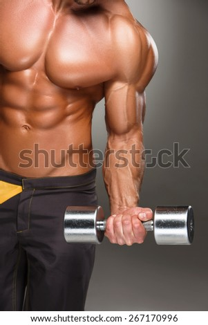Attractive male body builder with dumbbell on gray background. - stock photo