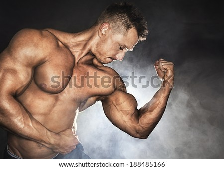 Attractive male bodybuilder showing his biceps - stock photo
