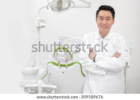 Attractive male distist smile in his dental clinic - stock photo