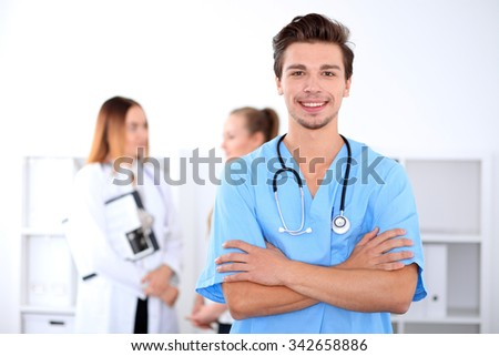 Attractive male doctor in front of medical group, crossed arms - stock photo