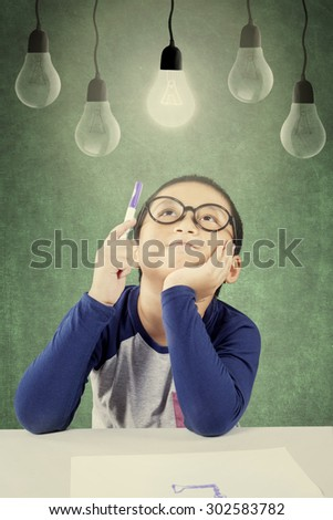 Attractive male elementary schoolboy thinking idea while holding a pen under a bright light bulb - stock photo