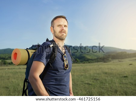 Attractive male hiker on hillside on sunset.