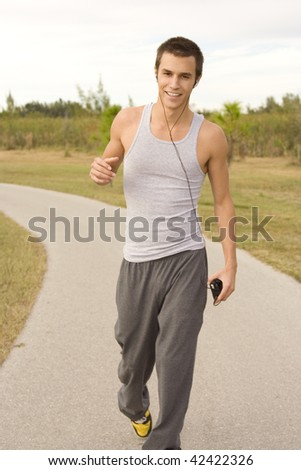 Attractive male jogger outside listening to music.