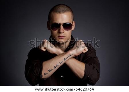Attractive male model - fashion concept portrait over dark background - stock photo