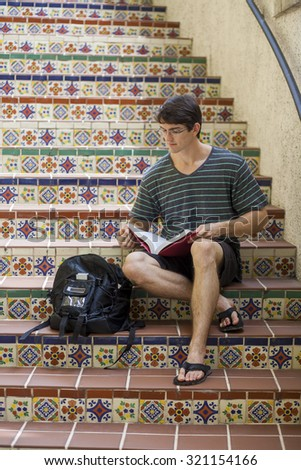 Attractive male student studying with textbooks on Spanish style tile steps, looking serious  - stock photo