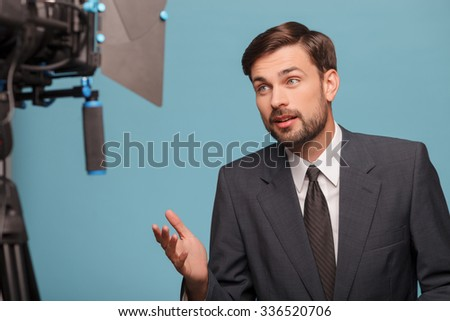 Attractive male tv newscaster is reporting and looking at the camera. He is smiling and gesturing. The man is wearing a suit. Isolated on blue background - stock photo