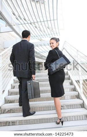 Attractive man and woman business team on stairs at office building - stock photo