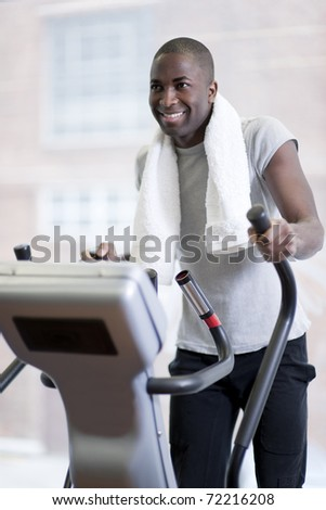 Attractive man at health club, exercising on stepper - stock photo