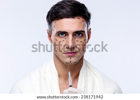 Attractive man at plastic surgery with syringe in his face - stock photo
