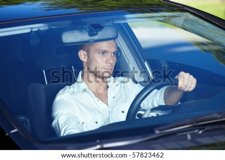 Attractive man behind the wheel of his car - stock photo
