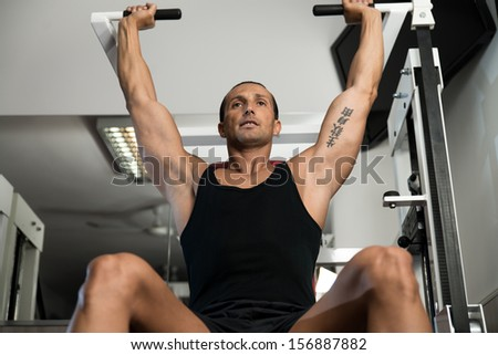 Attractive Man Doing Shoulder Press With Machine - stock photo