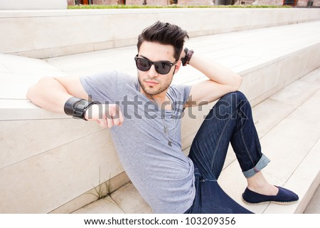 attractive man dressed casual posing outdoors - stock photo
