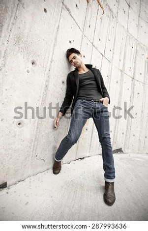 Attractive man dressed in jeans and boots in a grungy scenery - stock photo