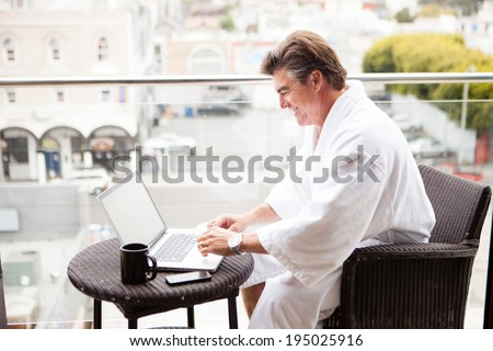 Attractive Man enjoying his morning coffee on his computer outside his hotel room - stock photo