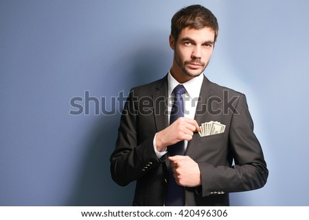 Attractive man getting dollar  banknotes out of suit pocket on grey background - stock photo