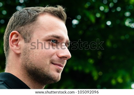Attractive man head profile with green tree on background - stock photo