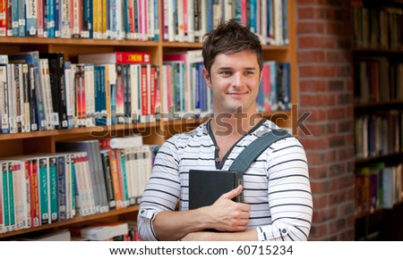 Attractive man holding a book in a book store - stock photo