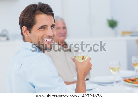 Attractive man holding a glass of white wine and looking at camera - stock photo