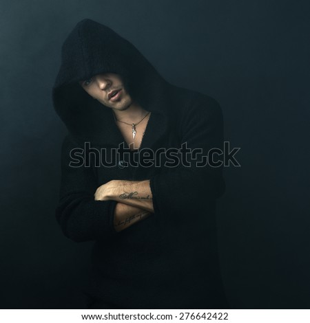 attractive man in a black hoodie crossed his arms - stock photo