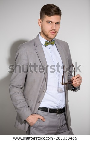 Attractive man in a suit and tie butterfly dress stylish sunglas - stock photo