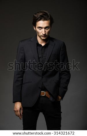 attractive man in black suit on dark background acting