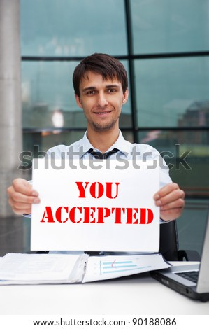 Attractive man in business suit with acceptance sign sitting at his office and smiling to camera