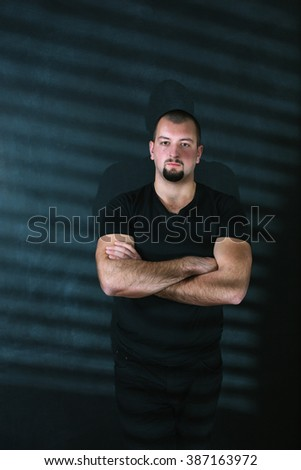 attractive man in shirt standing near the wall in the studio. lighting point light