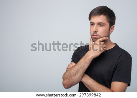 Attractive man is looking thoughtfully aside. He is touching his chin pensively. Isolated on grey background and copy space in left side - stock photo