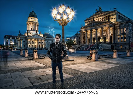 Attractive man is smoking a cigarette in Berlin in the evening - stock photo