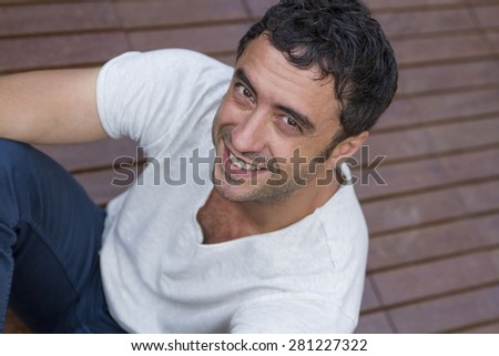 Attractive man of about thirty-five years old, white, posing sitting on wooden floor and looking smiling at the camera. Casual style.