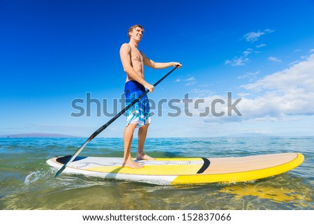 Attractive Man on Stand Up Paddle Board, SUP, Tropical Blue Ocean, Hawaii - stock photo