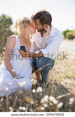 Attractive man proposing to his girlfriend in the country on a sunny day - stock photo