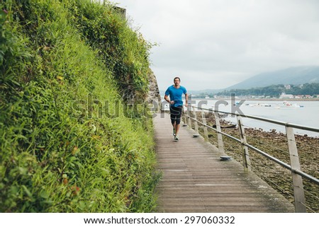 Attractive man running on a wooden walkway over the sea. Daily training. - stock photo