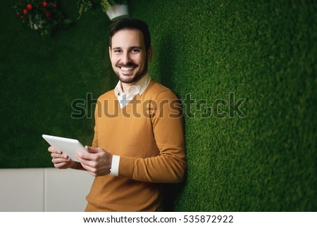 Attractive man standing over a green grass wall, holding a tablet