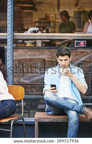 Attractive man using smart phone at cafe drinking coffee - stock photo