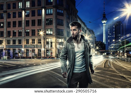Attractive man walks through the streets of berlin at night - stock photo
