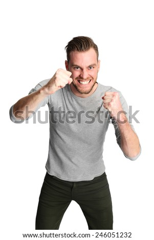 Attractive man wearing a grey shirt standing against a white background with raised fist. - stock photo