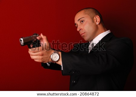 Attractive man wearing a suit aiming a gun. Red background. - stock photo
