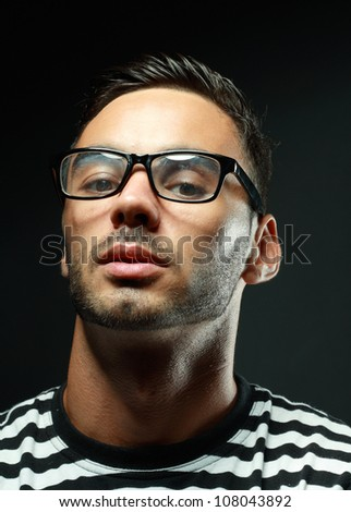 Attractive man wearing glasses over black background - stock photo