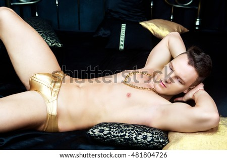 attractive man wearing golden chain and underwear in bed with black linen