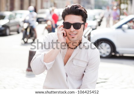 attractive man wearing sunglasses talking on mobile on the street - stock photo