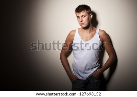 Attractive man wearing t-shirt - portrait on gray background. - stock photo