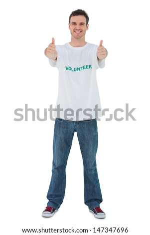 Attractive man wearing volunteer tshirt giving thumbs up on white background